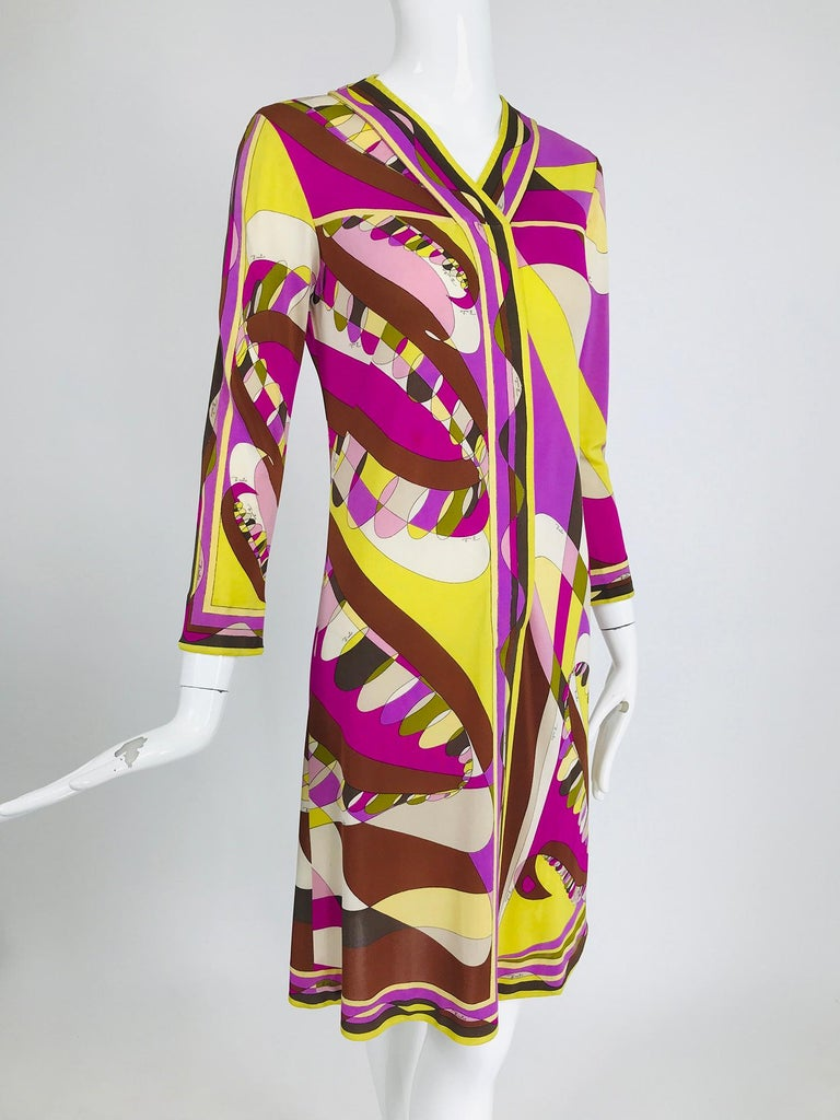 Vintage Emilio Pucci silk jersey print long sleeve day dress from the 1960s. Vibrant Pucci print in pink, chartreuse, brown, cream & fuchsia. Shift style dress with a V neckline, hidden button placket front and wrist length sleeves. The dress is