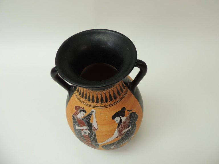 Vintage encaustic hand painted terracotta Greek water jug with handle. Tall hand painted jar depicting traditional Greek mythology figures and Greek key pattern in shades of white, black, pink, orange and gold.  Encaustic painting, also known as