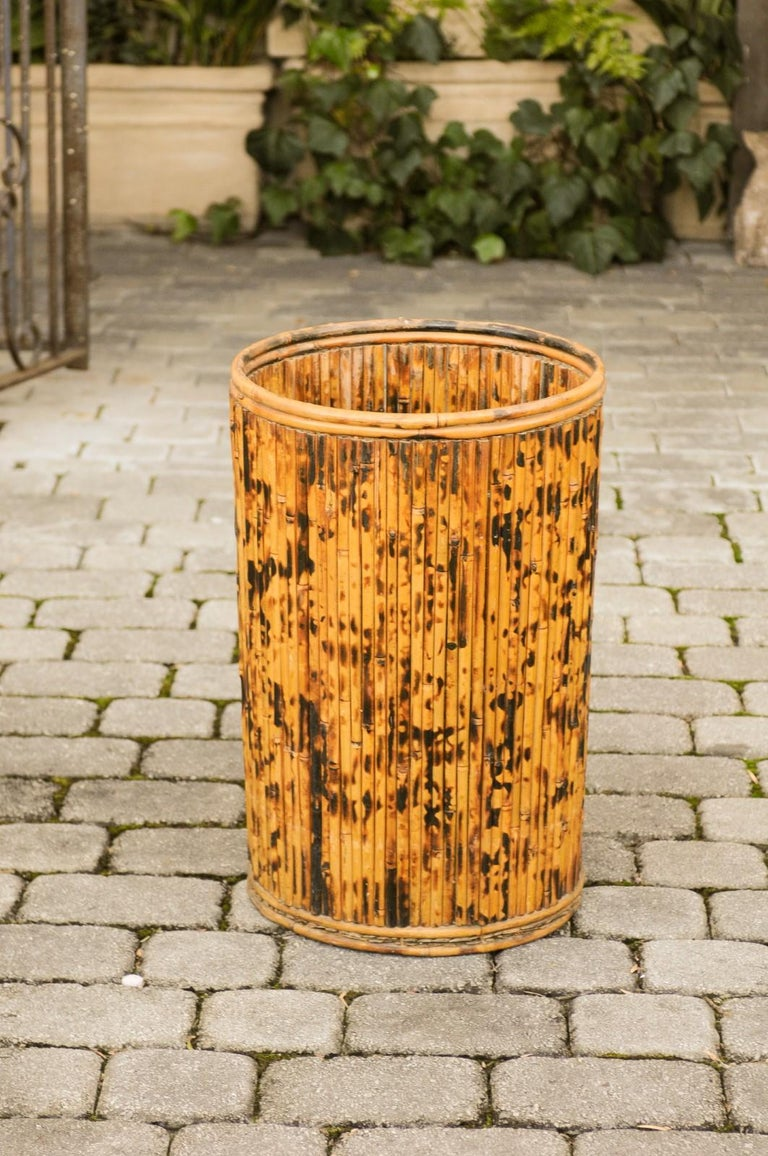 A vintage English bamboo umbrella stand from the mid-20th century, with mottled finish. Born in England during the midcentury period, this lovely bamboo stand is perfect to accommodate canes or umbrellas. Circular in shape, it is adorned with a