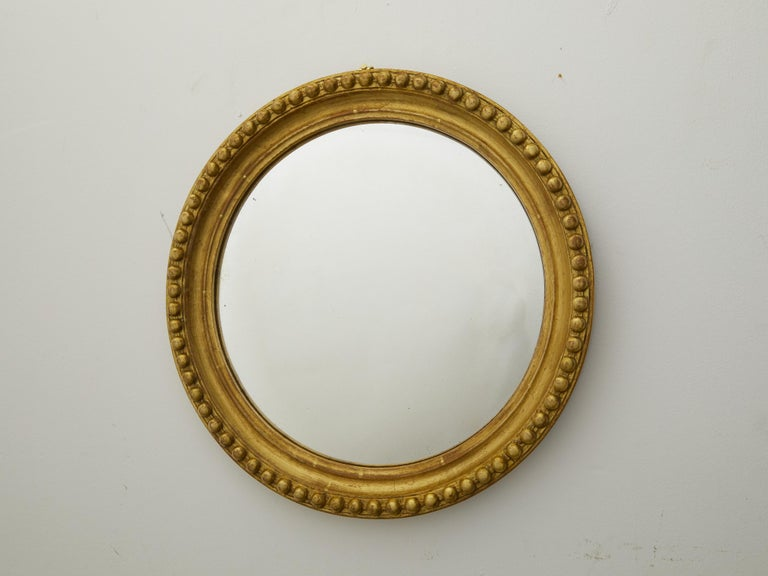 An English vintage giltwood convex mirror from the mid 20th century, with bead motifs. Created in England during the midcentury period, this mirror features a circular giltwood frame adorned with large beaded motifs, surrounding a convex mirror