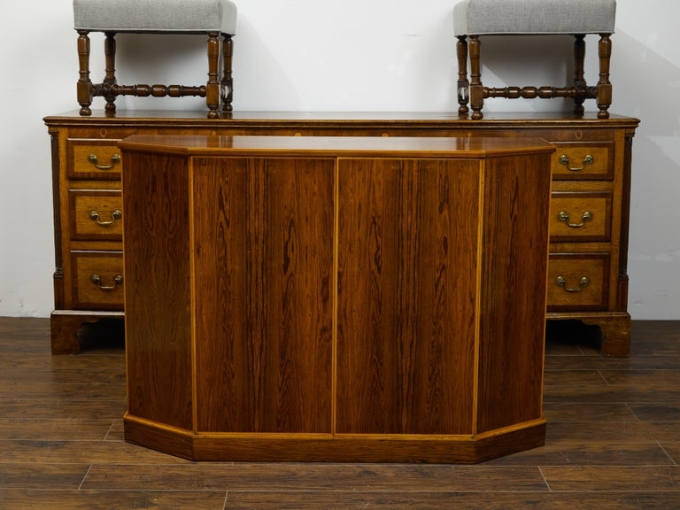An English vintage rosewood credenza from the mid 20th century, with canted panels. Created in England during the midcentury period, this rosewood credenza features a polygonal top sitting above two doors flanked with canted sides. These doors open
