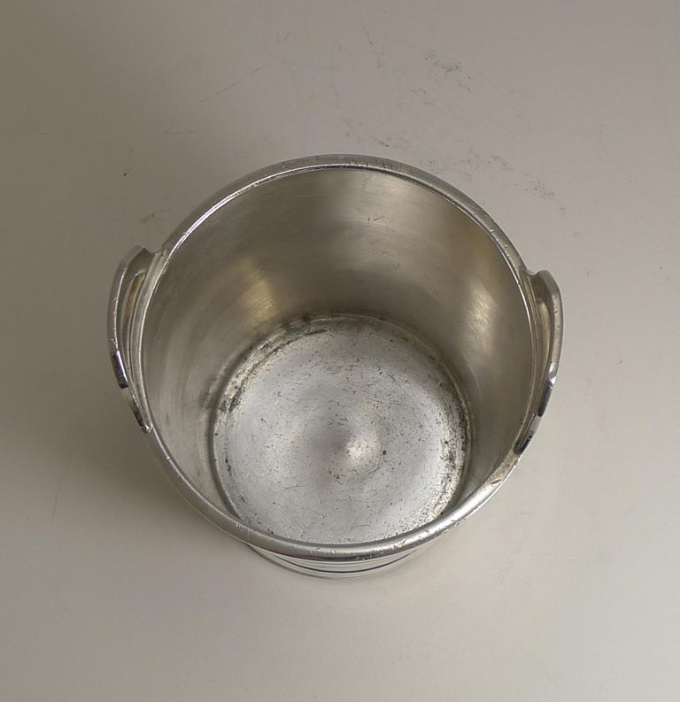 A very smart ice bucket to adorn the finest of bar carts and ready for cocktail hour.  Made from English silver plate, it was fashioned in the form of a traditional coopered wooden pail with handles, a lovely clean Art Deco look.  Made by the