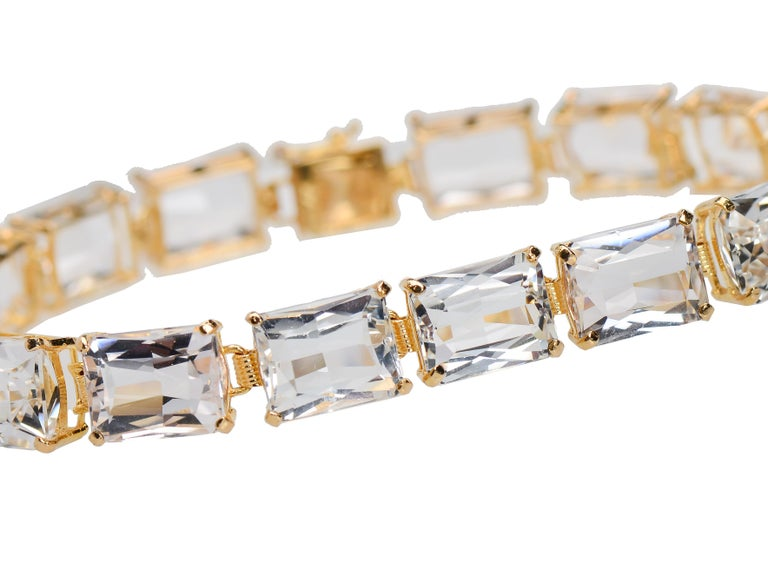 Set in 14 Kt gold, this bracelet of sixteen rectangular cut rock crystals is so sparkling and fresh, it is a river of the purest water from an underground spring. Each crystal is securely set in its cage of gold with small prongs at each corner so