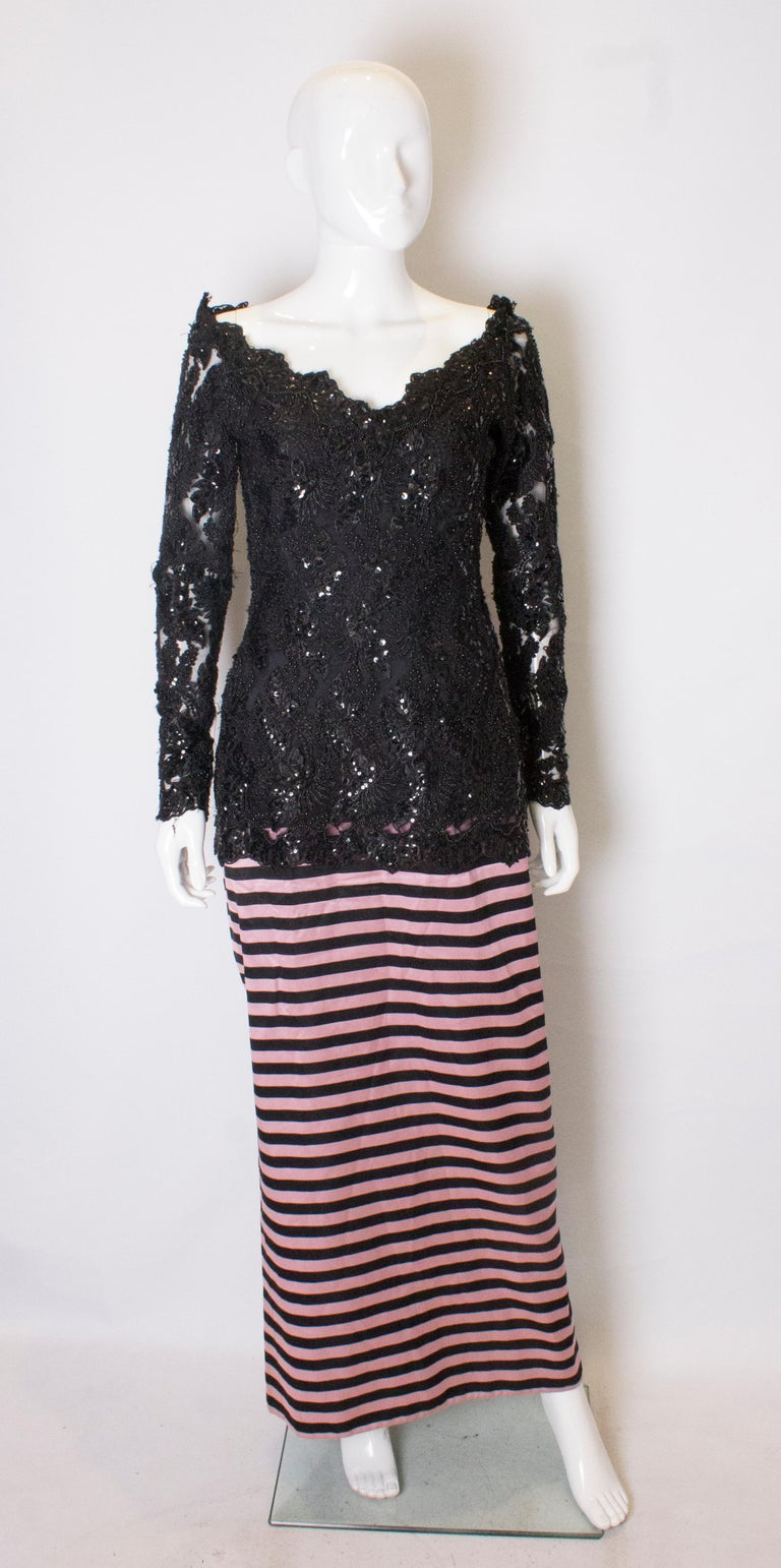 A headturning gown by Delores Couture. The upper part is heavily beaded , with a v neckline, and elastic under the shoulders, so enabling the dress to be worn off the shoulder . The skirt is in a pink and black strip with an 18'' slit at the back.