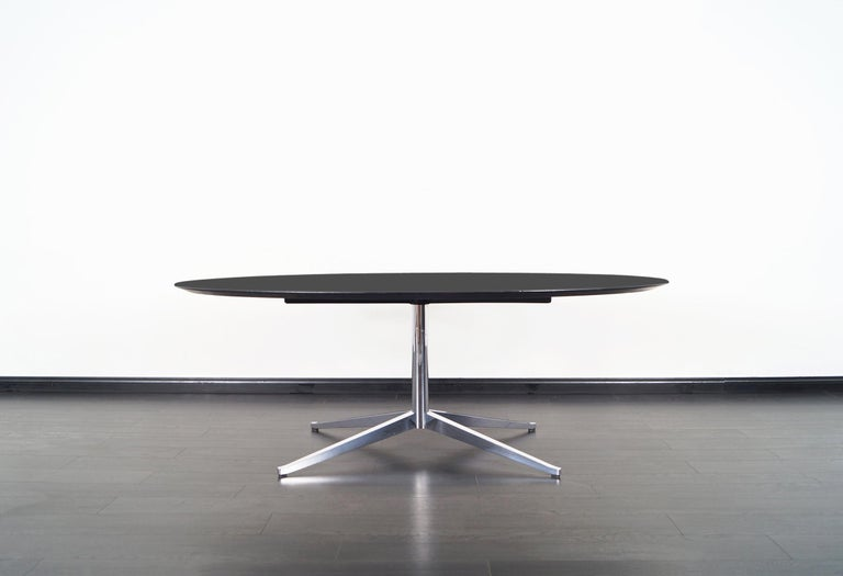 This amazing vintage table was designed by Florence Knoll for Knoll International in the United States, circa 1960s. Its versatile allows it to serve as a desk, dining table, or conference table. This iconic design features an ebonized top that sits