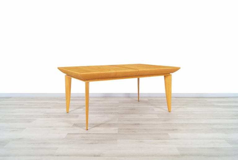 Vintage expanding oak dining table designed by architect and furniture designer Paul Laszlo for Brown Saltman in the United States. This spectacular dining table features an oak wood body with Laszlo's signature knife edge legs seen on his famous