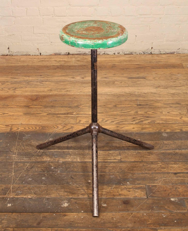 Vintage steel and distressed wooden factory shop stool, Industrial style with three steel poles and cast iron bubble pipe joint. Seat measures 11