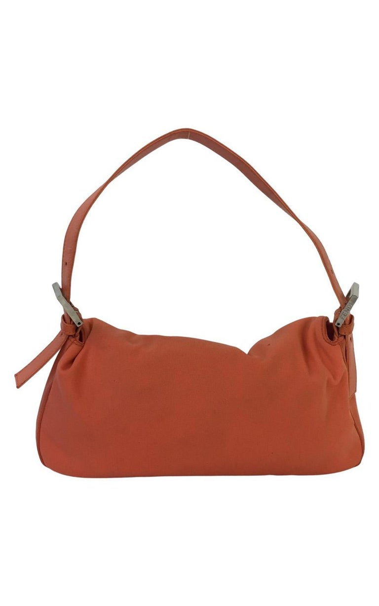 Fendi Baguette in Coral Nylon. The hardware is silver-colored. The bag has a flap and a FF fastening with a magnetic button. The inside is spacious and contains one pocket with a zip. The zipper is silver colored and contains a small Fendi pendant.