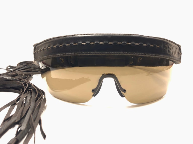 "Vintage Fendi limited edition leather constructed frame features a leather headband with tassels and tinted lenses.   This pair is marked ""FS341L 81 21 200 135 Made in Italy.  Produced and design in 1990's.  This piece has light sign of wear on the"