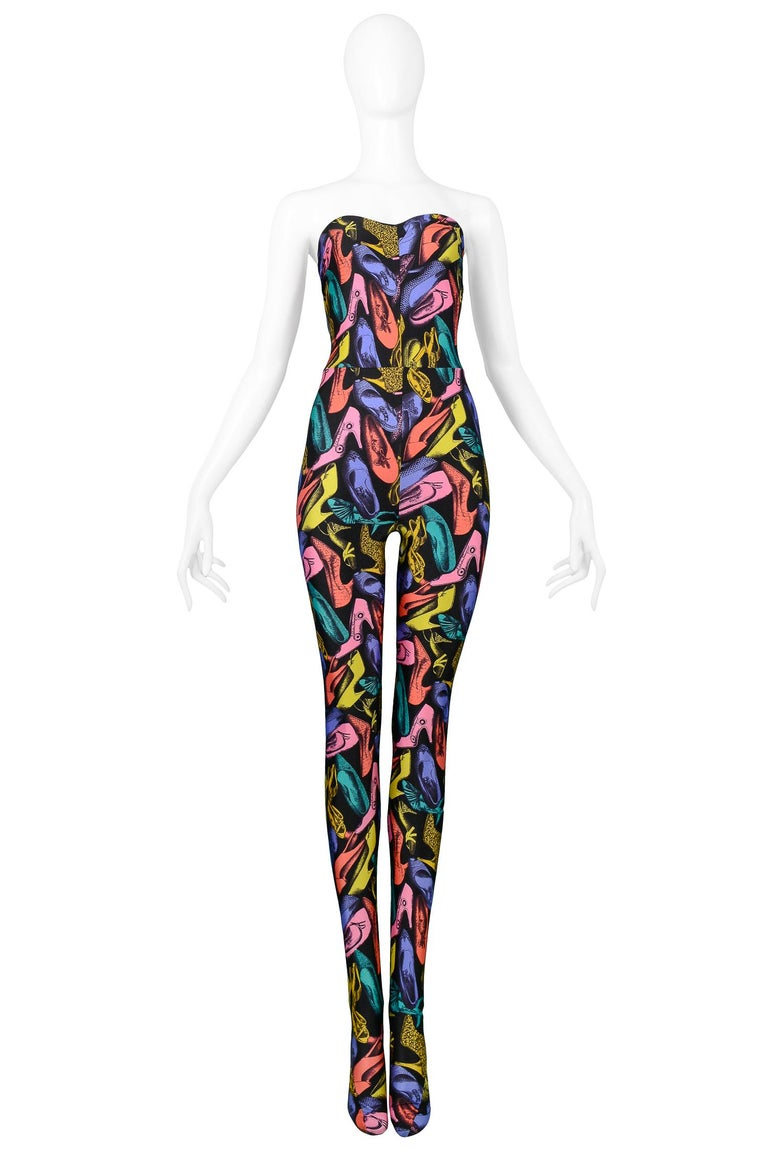 Vintage Salvatore Ferragamo multicolor shoe print silk jacket with lycra jumpsuit ensemble. The jacket features 3 gold buttons, high collar, fitted cut and is fully lined. The stretch lycra jumpsuit features a strapless sweetheart bodice and