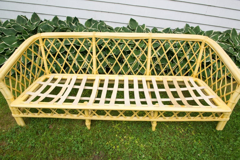 1970s vintage Ficks Reed faux bamboo and rattan sofa with a chinoiserie flair. In original yellow finish with original fabric. Cushions have hardened with age. In remarkable condition. Arm height is 21