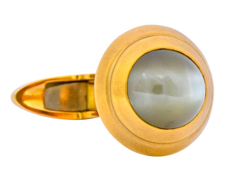 Each cufflink centering a round cabochon cat's eye chrysoberyl measuring approximately 9.0 mm  Cat's eye chrysoberyl are grayish-green and yellowish-green in color with striking chatoyancy featuring milk and honey phenomena  Bezel set in a matte