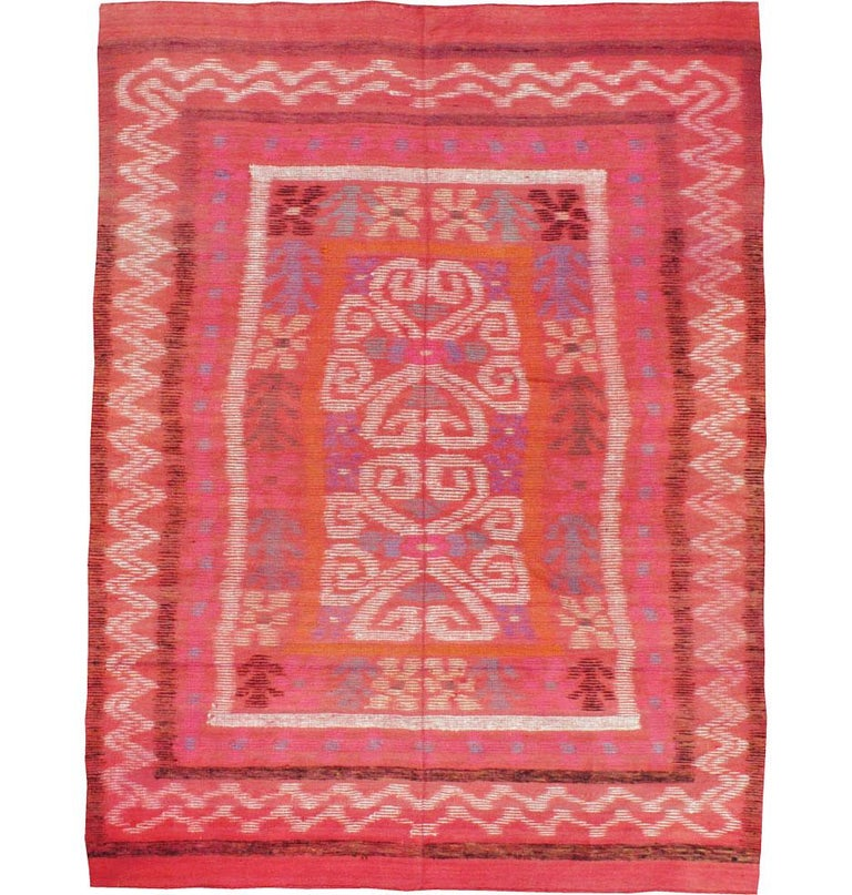 A vintage Finnish Kilim handmade during the mid-20th century in an accent rug size. The Scandinavian Modern design of abstract and geometric floral patterns and zigzags sits atop a primarily coral red field. A protective backing has been placed to