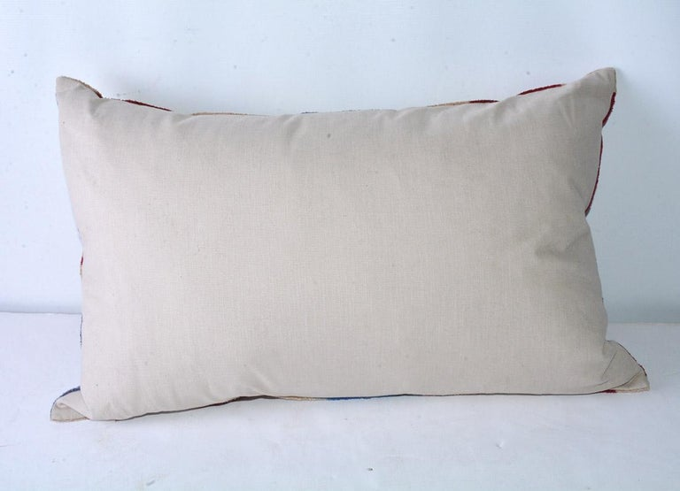 The vintage lumbar pillow is covered on the front with a flame stitch design in red, blue and beige chenille cotton. The back is of beige cotton. A zipper encloses an inner feather pillow. An accent for the sofa with character.