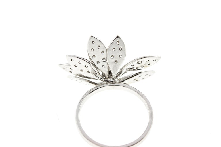 This vintage style floral cocktail ring is made in white gold and features diamonds on the leaves and petals.  A total carat weight of .56 diamonds are encrusted on the ring's petals.