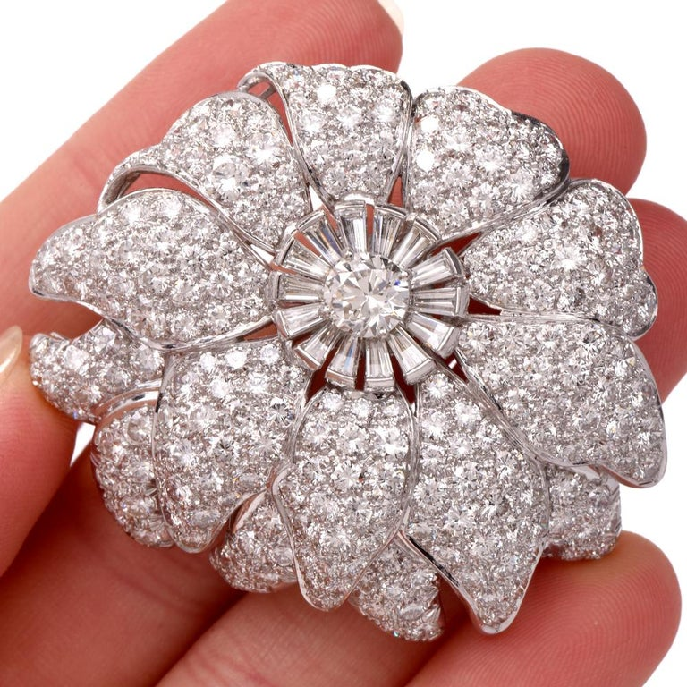This meticulously crafted and versatile lapel brooch and pendant simulates an enchanting flower head with multiple petals rendered in solid platinum. With remarkable glitter, this exquisite monochromatic piece of jewelry is centered with a 0.70