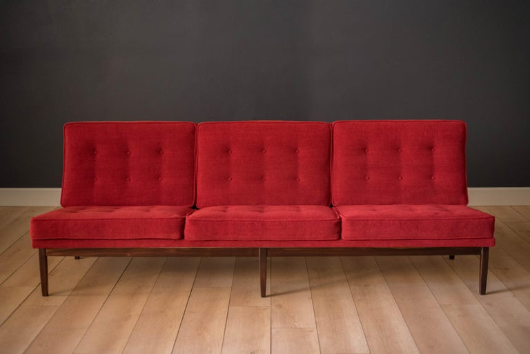 Mid-Century Modern sofa by Florence Knoll for Knoll, model 2553 RW. This piece was designed with a custom rosewood frame and original red crimson textile fabric. Seat cushions are supported by springs built to last and are hand sewn to the