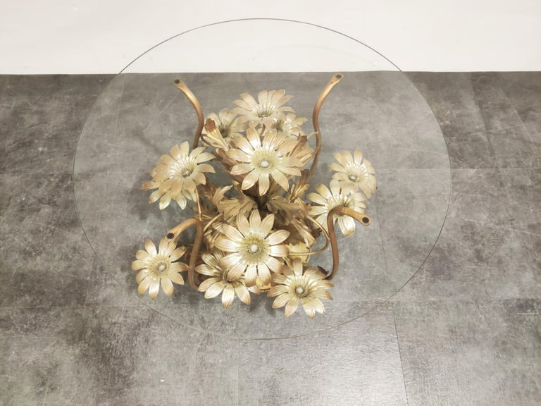 Charming metal flower coffee table with a round clear glass top.  The table was manufactured in Italy.  Beautiful elegant look which brings a touch of nature inside your home.   Good condition, some paint loss.  1960s, Italy  Measures: