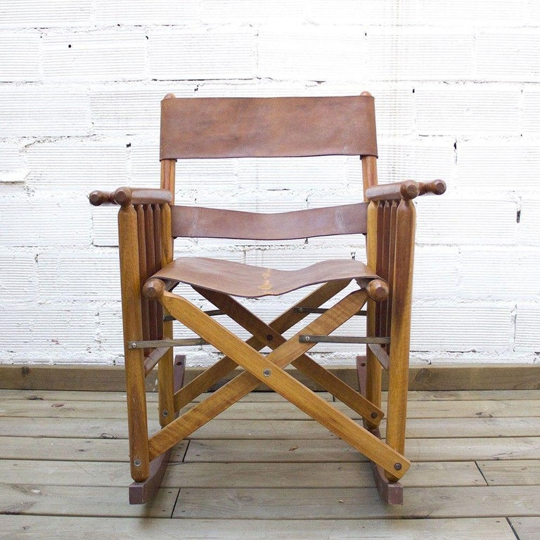 A Safari style craftsman rocking chair with beautiful woodworking and leather panelling details. This 1970s vintage rocking chair has many wooden spindles connecting the armrests to the long rounded rocking chair bottom. The seat and backrest are