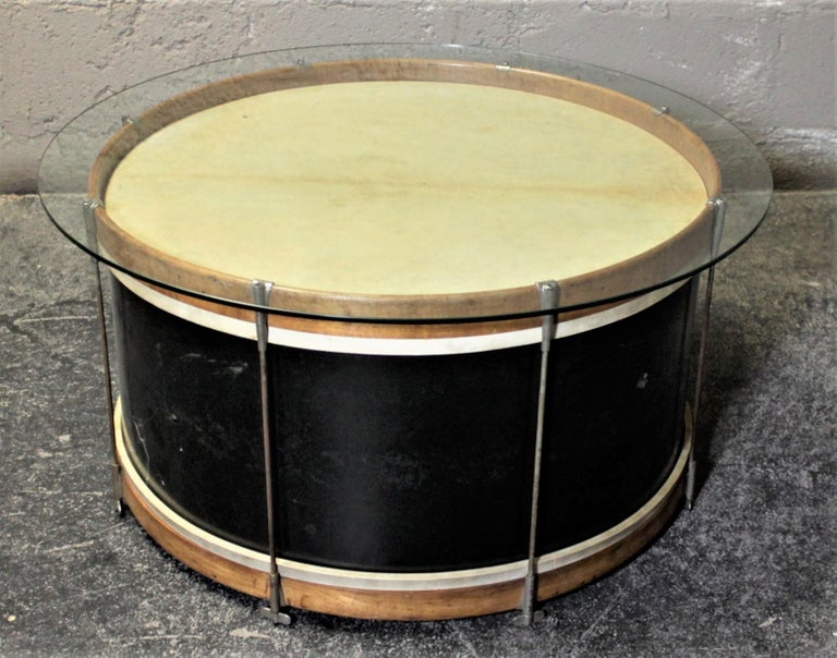 This novel Folk Art glass topped drum coffee or cocktail table has no maker's tag on it, but it is presumed to have been made in the United States in circa 1940s. This vintage bass drum has natural wood rims a painted wood body and chrome lugs. The