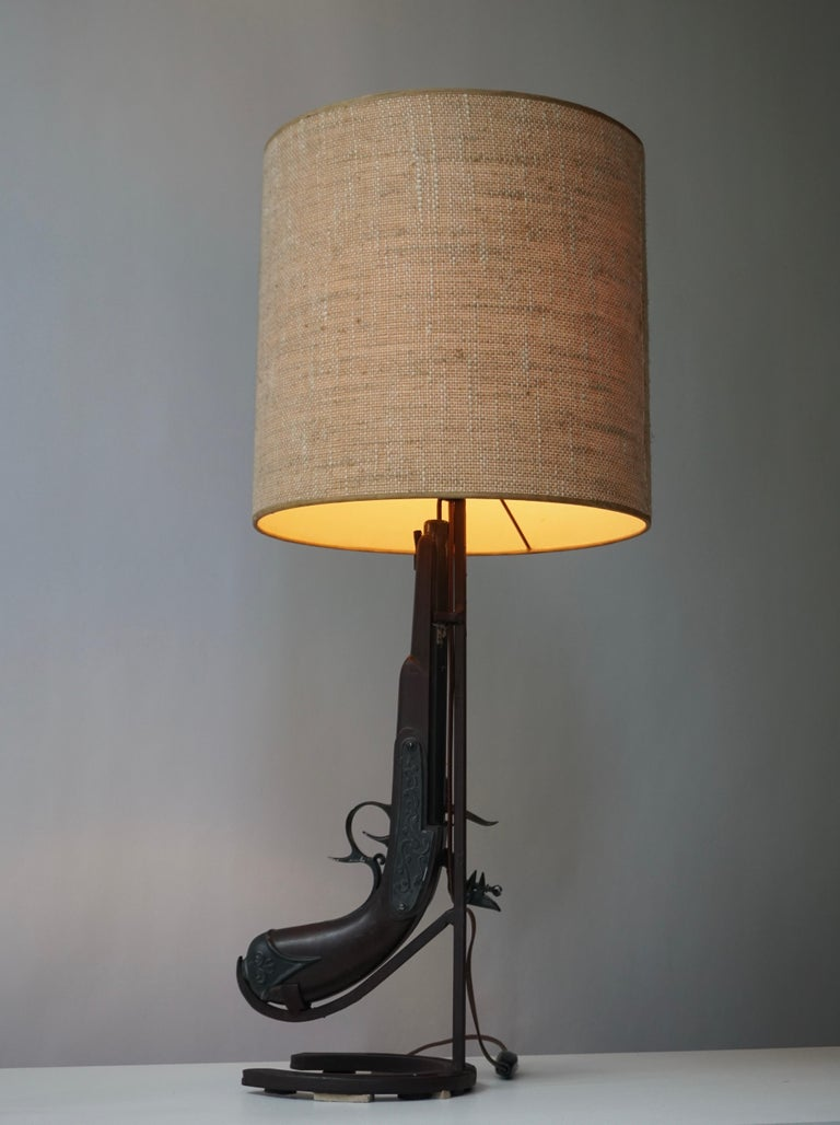 Vintage Folk Art table lamp handmade in the shape of a gun/ rifle using wood and wrought iron and having an antique horseshoe mounted as the front sight.  Measures: Height 70 cm. Diameter 30 cm.