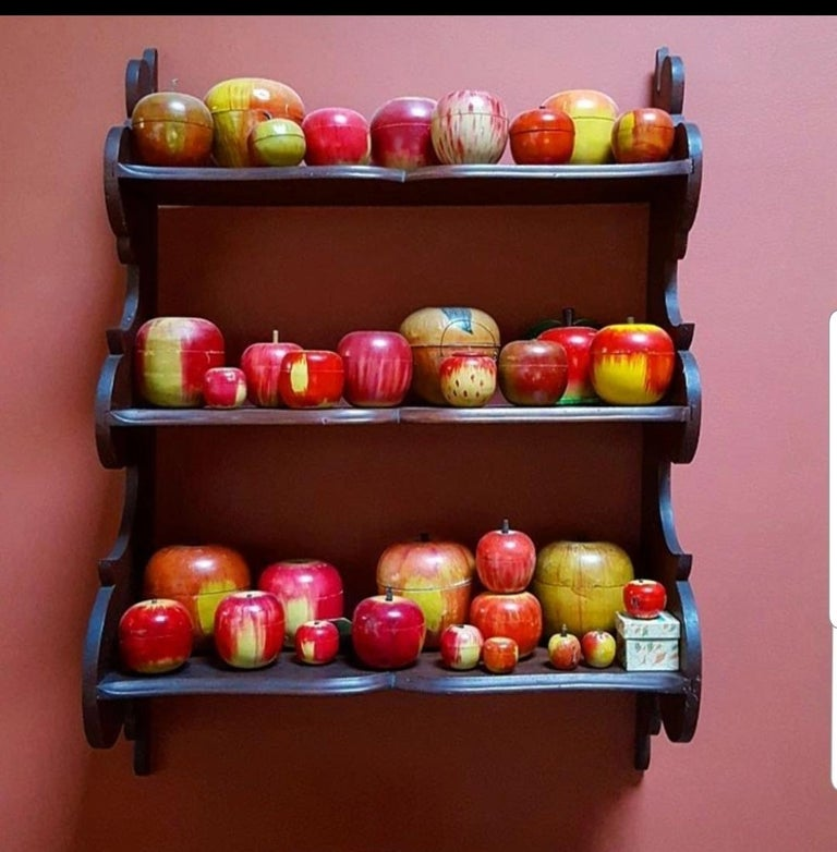 Here is a lifetime collection of 62 painted apples made mostly as covered boxes for children to play with. Most of the apples are wooden, one is a set of nesting apples, several contain a roulette wheel, a few still have tiny spinning tops or pink