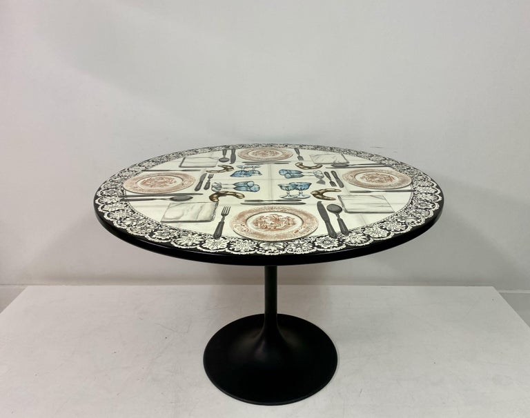 Diningor centre table  By Piero Fornasetti  Lithographically printed top  Silvered cutlery  Black powder coated base  Signed on top  Italy 20th century.