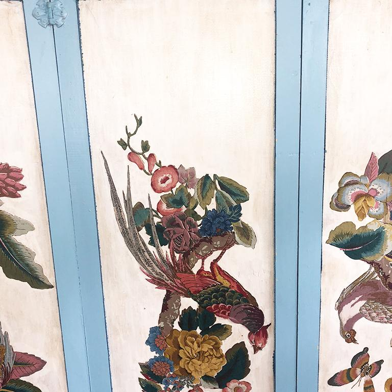 Folding divider screen featuring colorful birds and flora on the front side. The back is upholstered in cloth and trimmed with intricate darker blue trim. Birds and floral on front are applied to wood on a cream background.