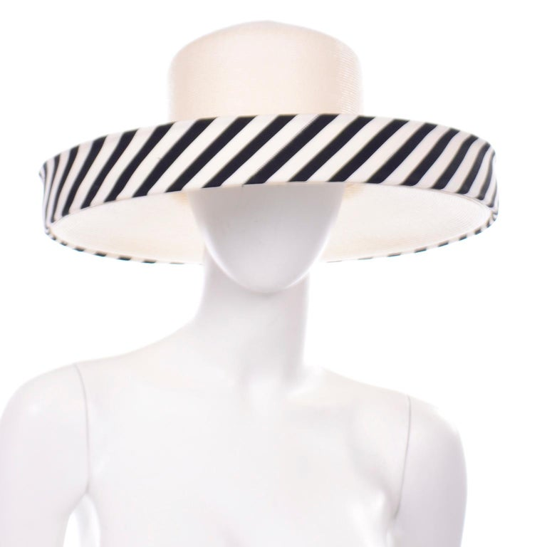 This sensational vintage ivory woven summer hat has an upturned brim that is lined with black and white stripes. There is a small knotted bow on the side and the hat has the Frank Olive for Saks Fifth Avenue label. This incredible Frank Olive hat os