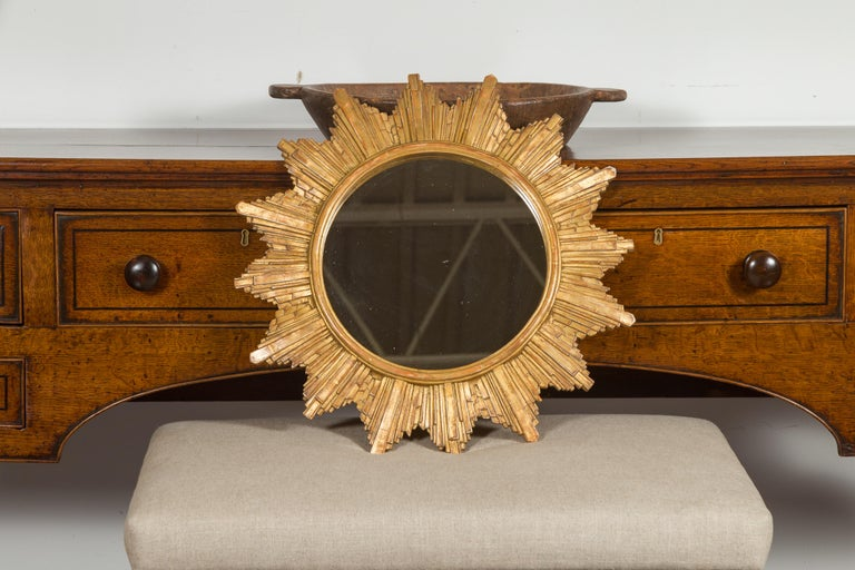 A French vintage gilt composition sunburst from the late 20th century, with rays of varying sizes and flat mirror. Born in France during the 1970s, this sunburst features a clear mirror plate surrounded by a molded inner frame, from which are