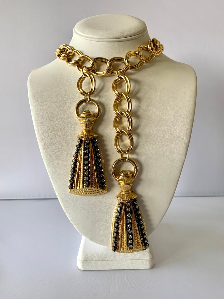 New old stock French gilt-metal tassel versatile necklace featuring a thick gold link chain which is accented by two large cast metal tassels adorned with black enamel and large Swarovski diamante rhinestones. The necklace can also be worn as a belt