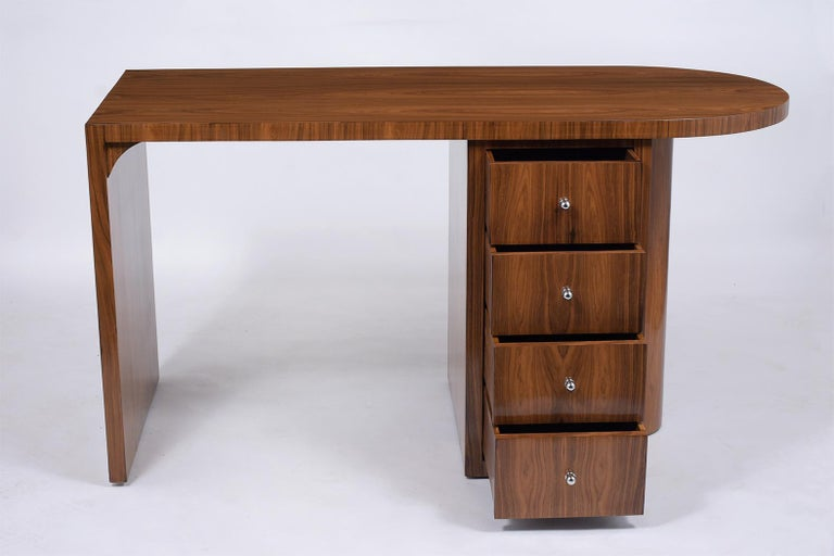 An extraordinary vintage Art Deco desk finely crafted out of exotic kingwood with a newly lacquered finish and is fully restored. This writing table is eye-catching features an L design with a stylish oval top, and a pedestal cabinet that comes with