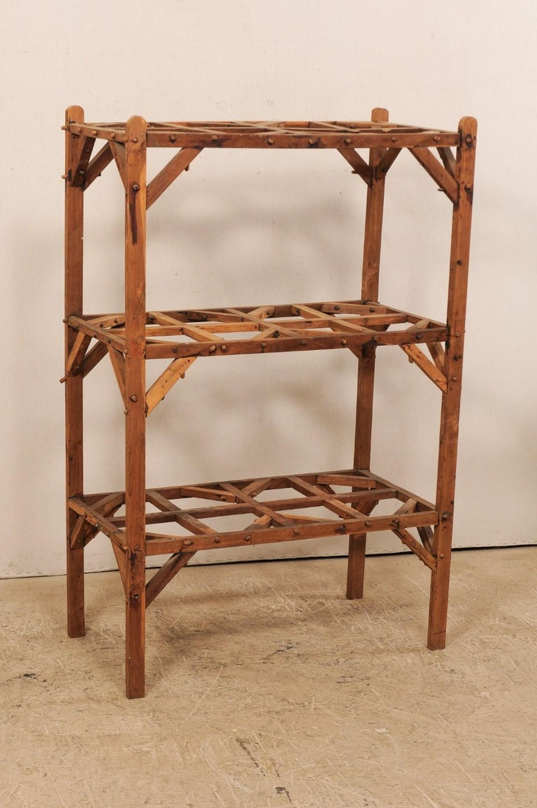 A French artistically designed wood open shelving unit from the mid-20th century. This vintage shelf from France, standing just under 5.5 feet in height and almost 2 feet deep, features two open, interior shelves, along with the additional top