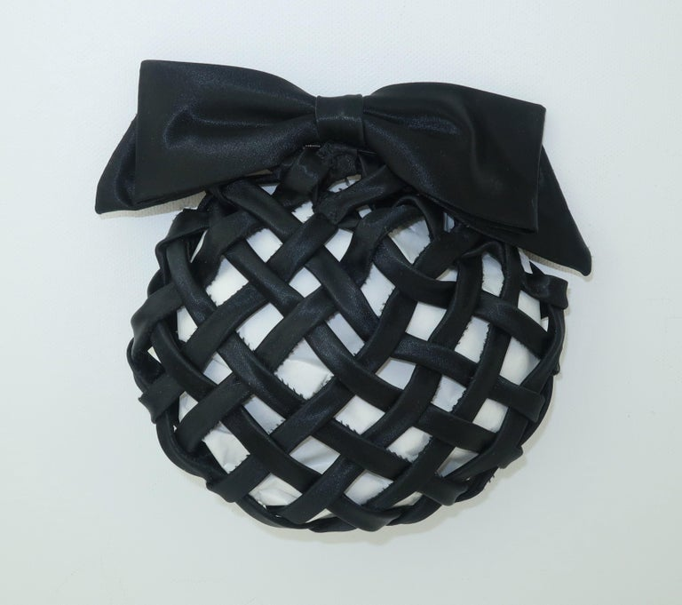French black satin hair ornament in the form of an easy to use clip or barrette.  The black satin ribbon is woven into a lattice design, lined with an elasticized cord and finished with a bow.  The clip hardware opens with a squeeze on one end and
