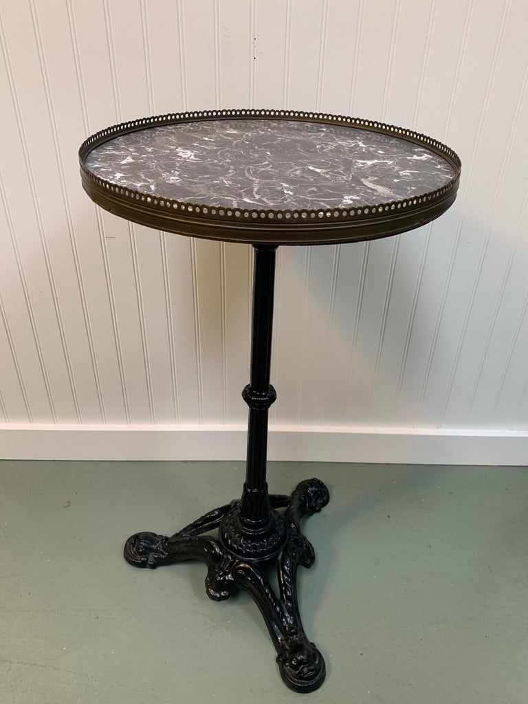 Early 20th century French cafe bistro table with cast iron pedestal. Original marble top with brass fencing around, in great condition. This piece would be ideal in a breakfast nook or as an outdoor garden table. Diameter: 16.25