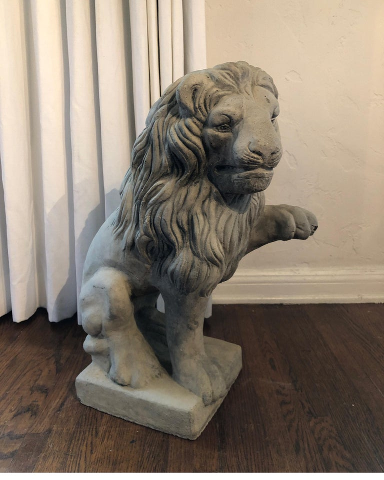 Mid-20th century cast stone garden sculpture lion seated on plinth with one paw raised. Beautiful detail of head and mane. Some natural patina and works great for interior or exterior.