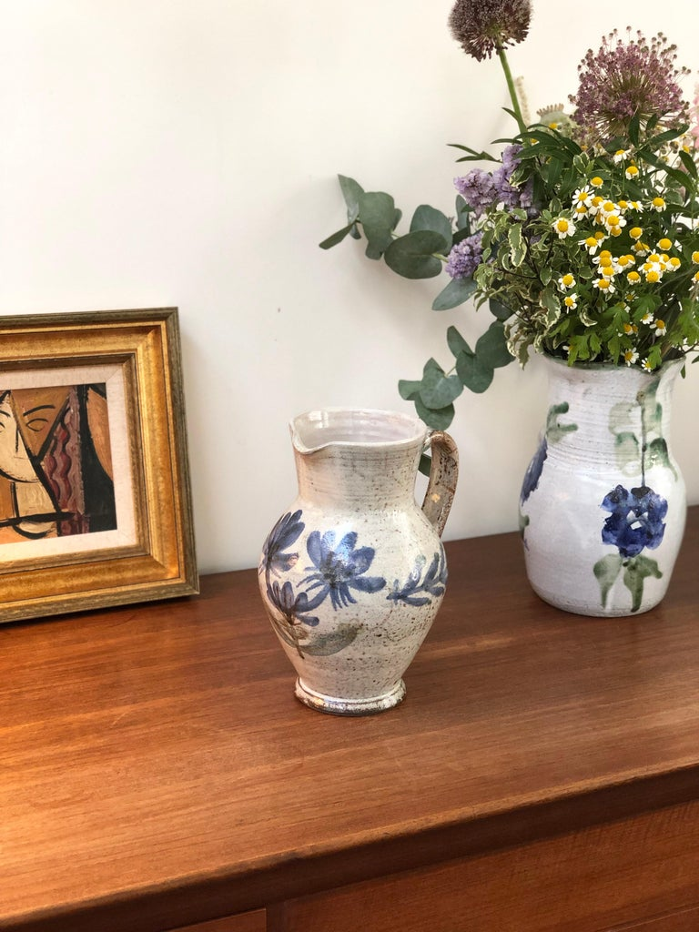 Vintage ceramic pitcher / vase by Gustave Reynaud, Le Mûrier, circa 1950s. This utilitarian pitcher is also a delightful work of art doubling as a beautiful vase. On the rustic exterior you will find lovely flowers with blue petals under the spout