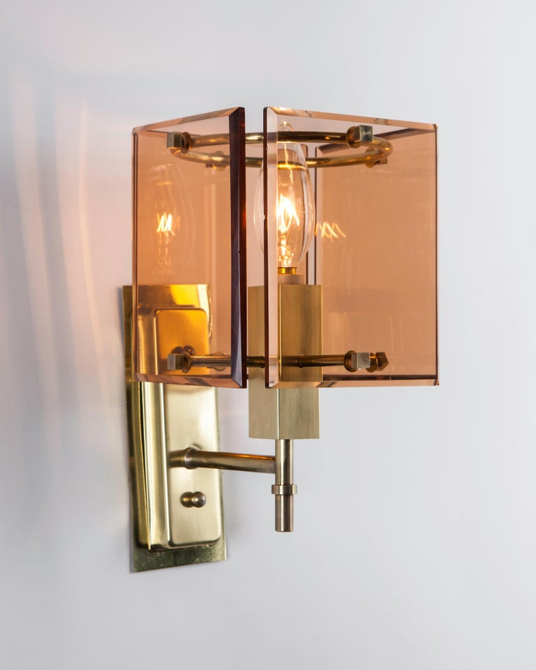 AIS3110 A pair of vintage French Deco sconces with square rose glass panel shades which create a wonderful warm glow. Small cube fasteners hold the glass onto rectangular brass frames in their original soft worn polished finish. Due to the antique