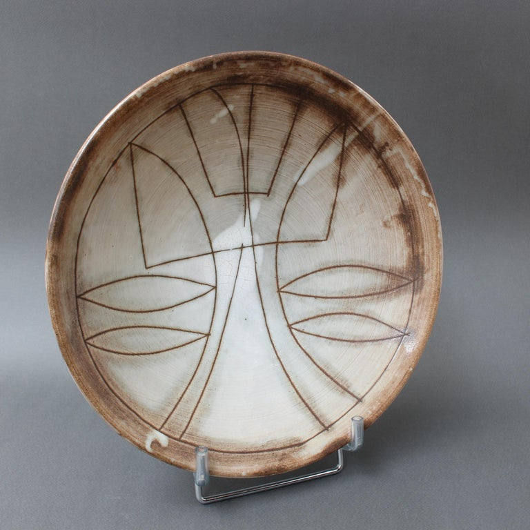 Mid-century decorative bowl (circa 1960s) by Jacques Pouchain - Atelier Dieulefit. This elegant bowl, elevated by a small circular base, was created in Pouchain's trademark tones and glaze. The bowl's recess is decorated with a stylised flower in