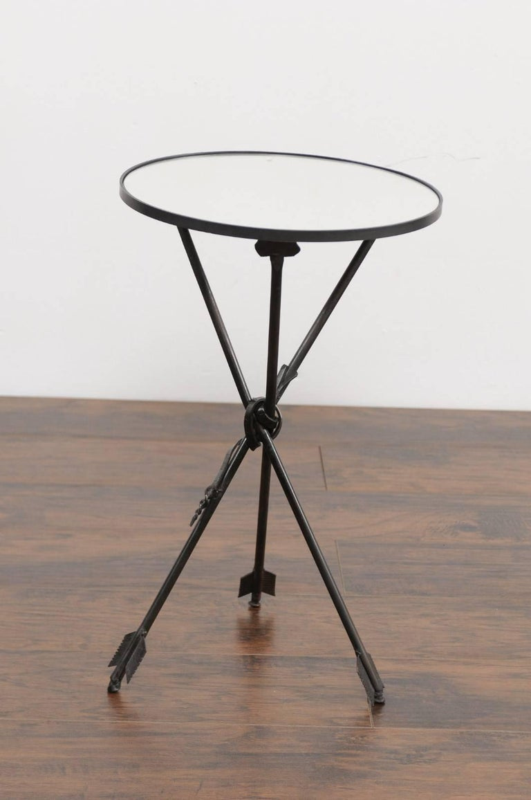 A French vintage round iron side table from the first half of the 20th century with arrow legs and new mirrored top. This French side table features a circular top, adorned with a new custom-made mirror. The table is raised on an exquisite black