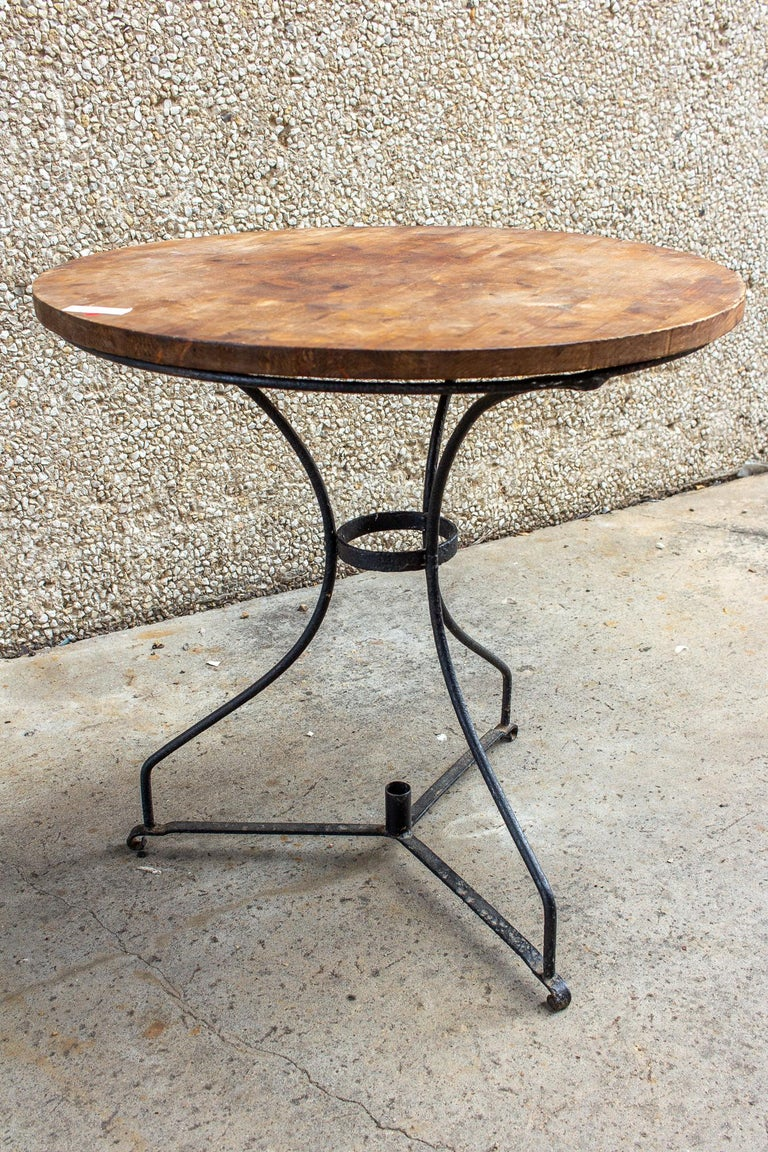 This is a vintage French garden table with a black iron base and a solid wood top. The top is likely newer than the base, as the base is made to accommodate an umbrella, but there is no opening in the tabletop. The wood top has a rich chocolate