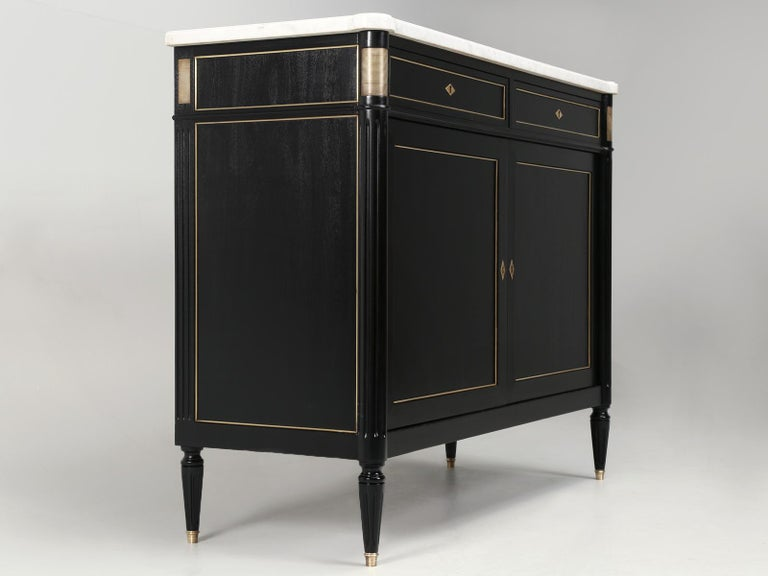 French vintage Louis XVI style 2-door buffet that has just emerged from our restoration department. After going through an exhaustive structural inspection, we moved the French Louis XVI buffet into our Old Plank finishing department, where we