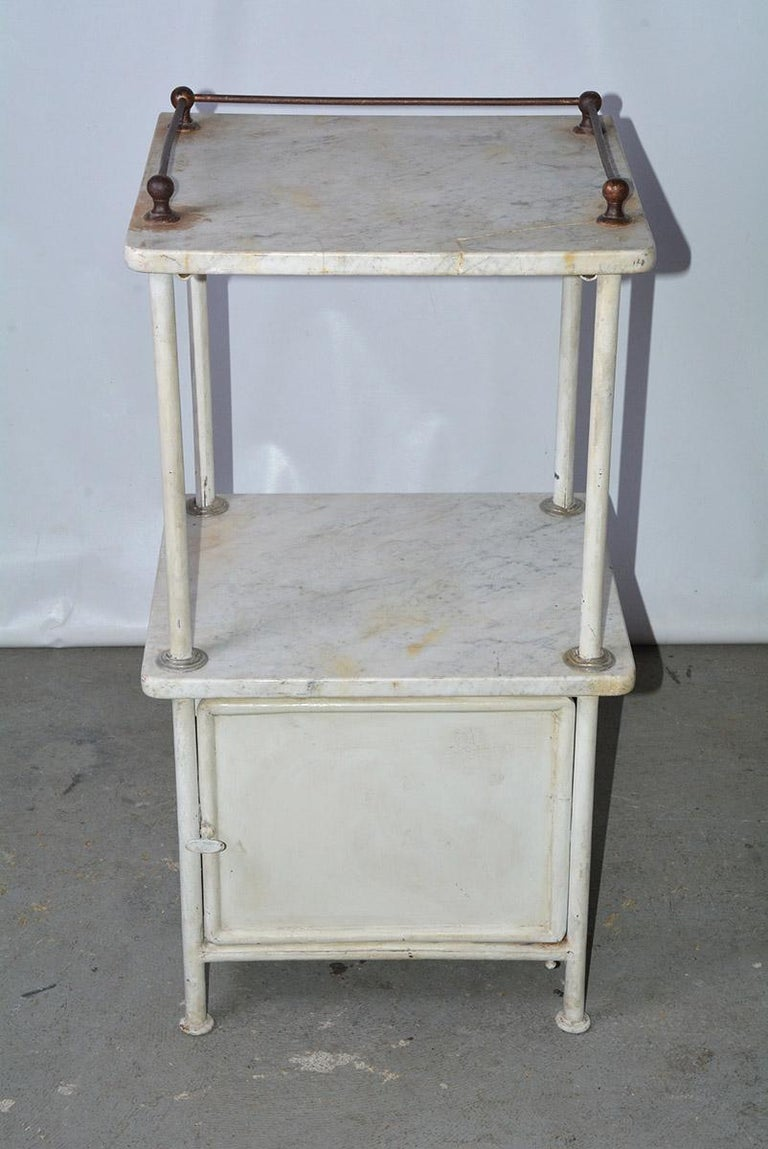 The vintage metal night stand or medical cabinet has two veined marble shelves, the top one having a metal railing on three sides. Below the bottom shelf is a metal storage cabinet. Perfect additional storage and shelving for the bathroom, kitchen,