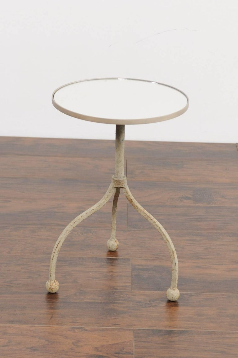 A French vintage painted iron round side table from the mid-20th century with tripod base and new mirrored top. This French side table features a circular top, supporting a new custom-made mirror. The table is raised on an interesting iron base,