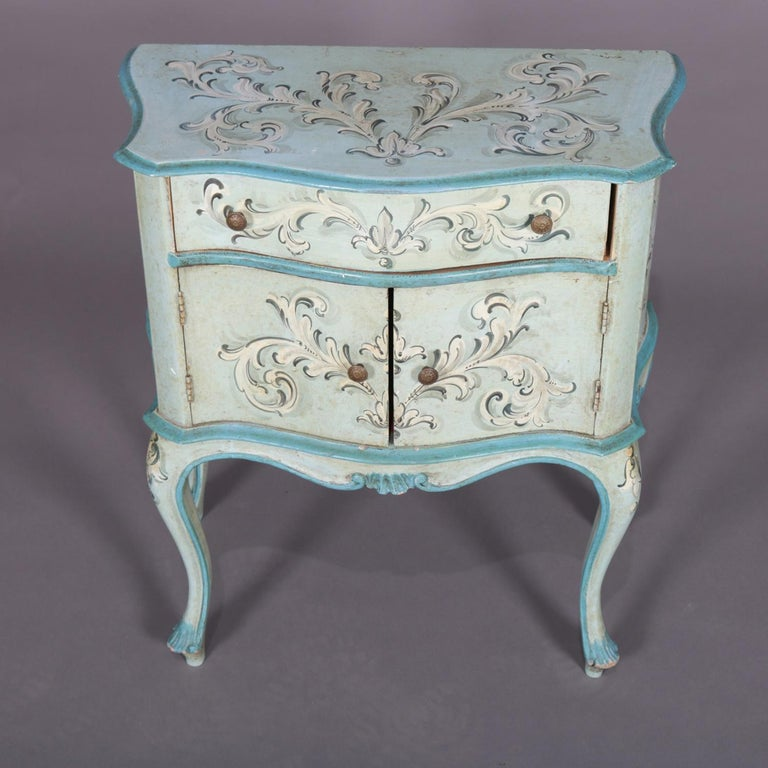 A vintage French provincial style by Florentia features serpentine form with upper frieze drawer over double door cabinet hand painted with foliate, scroll and acanthus decoration, raised on cabriole legs, en verso original label