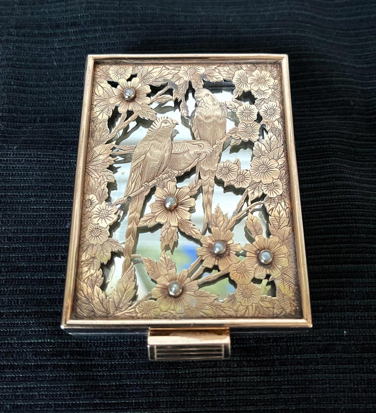 A stunning silver compact case with gilt by Boucheron Paris circa 1930s-1940s, of Art Deco period and style. The silver case features an iconic façade with a pierced and chased three parrots perching on flowering branches set with five mini pearls.
