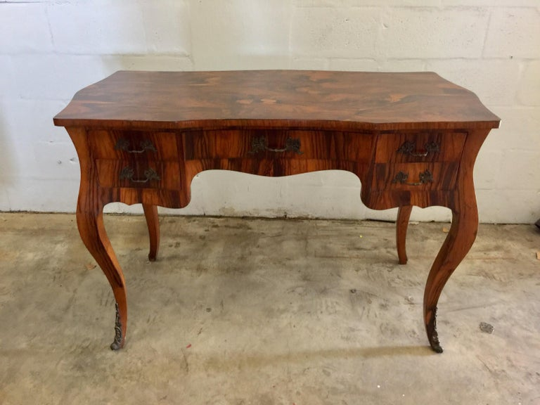 A vintage French desk or writing table. Beautiful Acacia burled wood grain. USA, circa 1960.  Features five drawers and patinated metal hardware.