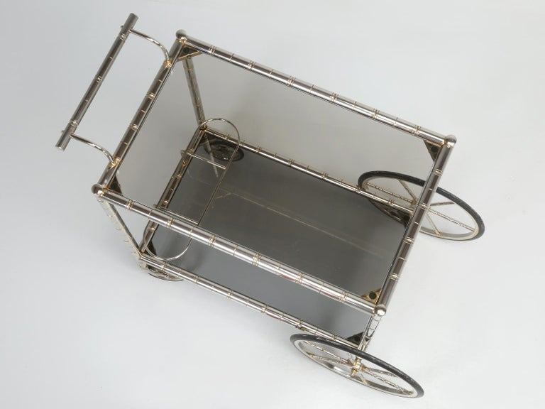 Vintage French tea cart or bar cart constructed of steel that was brass-plated, but over the years you can clearly see where the brass plating has worn off the tea cart and left it with a wonderful old patina. The glass should be replaced. Height