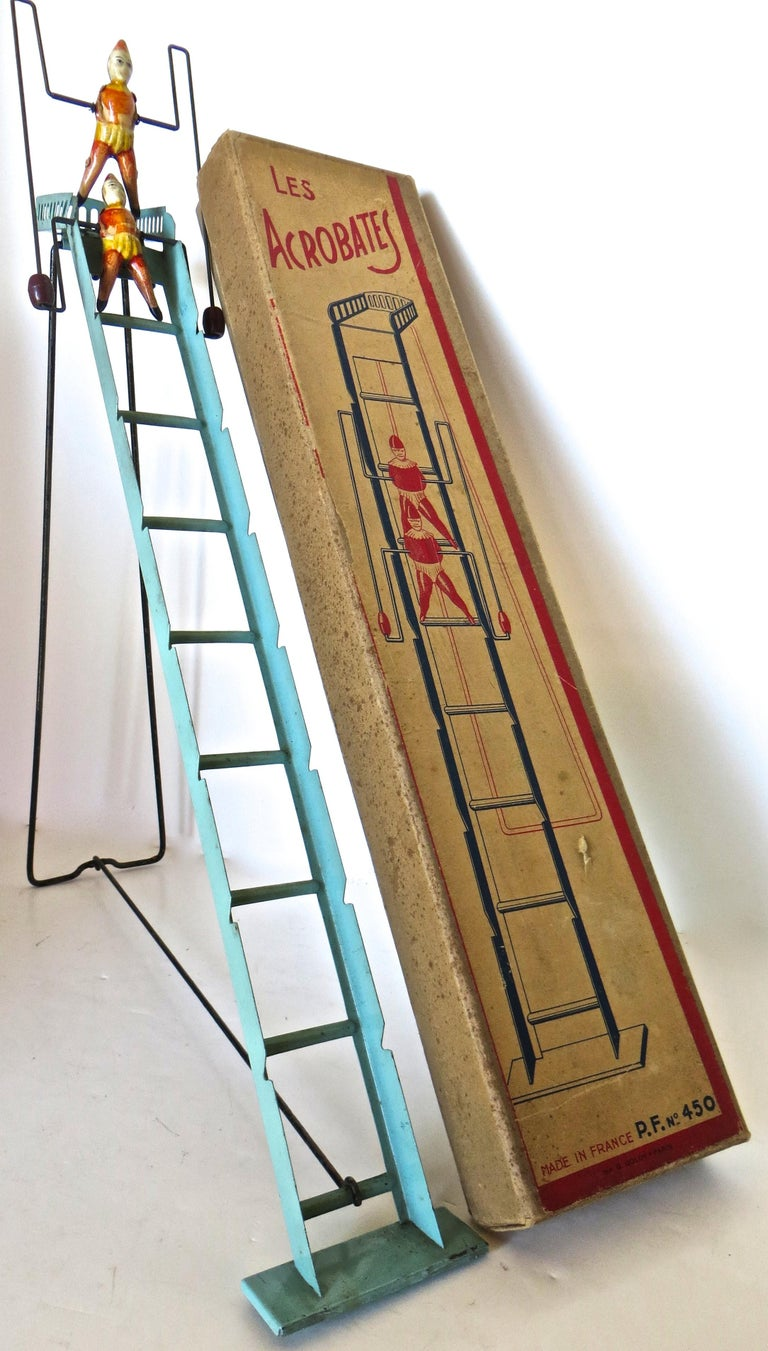 Rare 100 year old French toy in it's original box depicting two acrobats attached to a wire frame with brown barrel weights, cascading down a green metal ladder. Once assembled (loop the hand-painted black support frame over the bottom rung of the