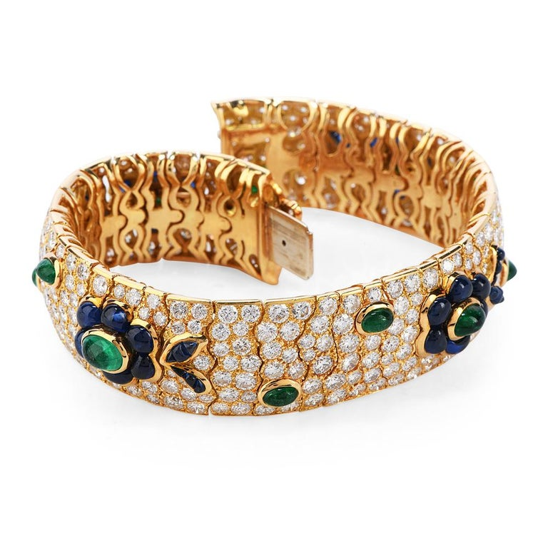 his French madeDiamond,Emeraldand Sapphire bracelet is sure to makea Statementin any room.  Wide throughout and flexiblle bangle bracelelt, this 18k yellow goldbracelet has manylinks covered with Pave' setdiamonds andflowerpatterns of